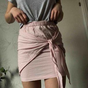 En fin ljusrosa kjol från Andrea Hedenstedt's kollektion med NAKD. Går att knyta på olika sätt. Den är lite liten nedtill för mig, därför aldrig använd. Frakt tillkommer eller mätas i Karlstad
