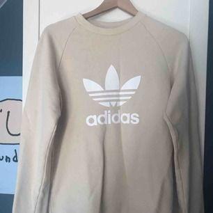 Beige Adidas tröja, aldrig använd, passar S och M.  Möts upp i Stockholm eller frakt (köpare står för frakt).