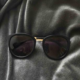 Svarta solglasögon med gulddetaljer. Inga repor eller defekter.
