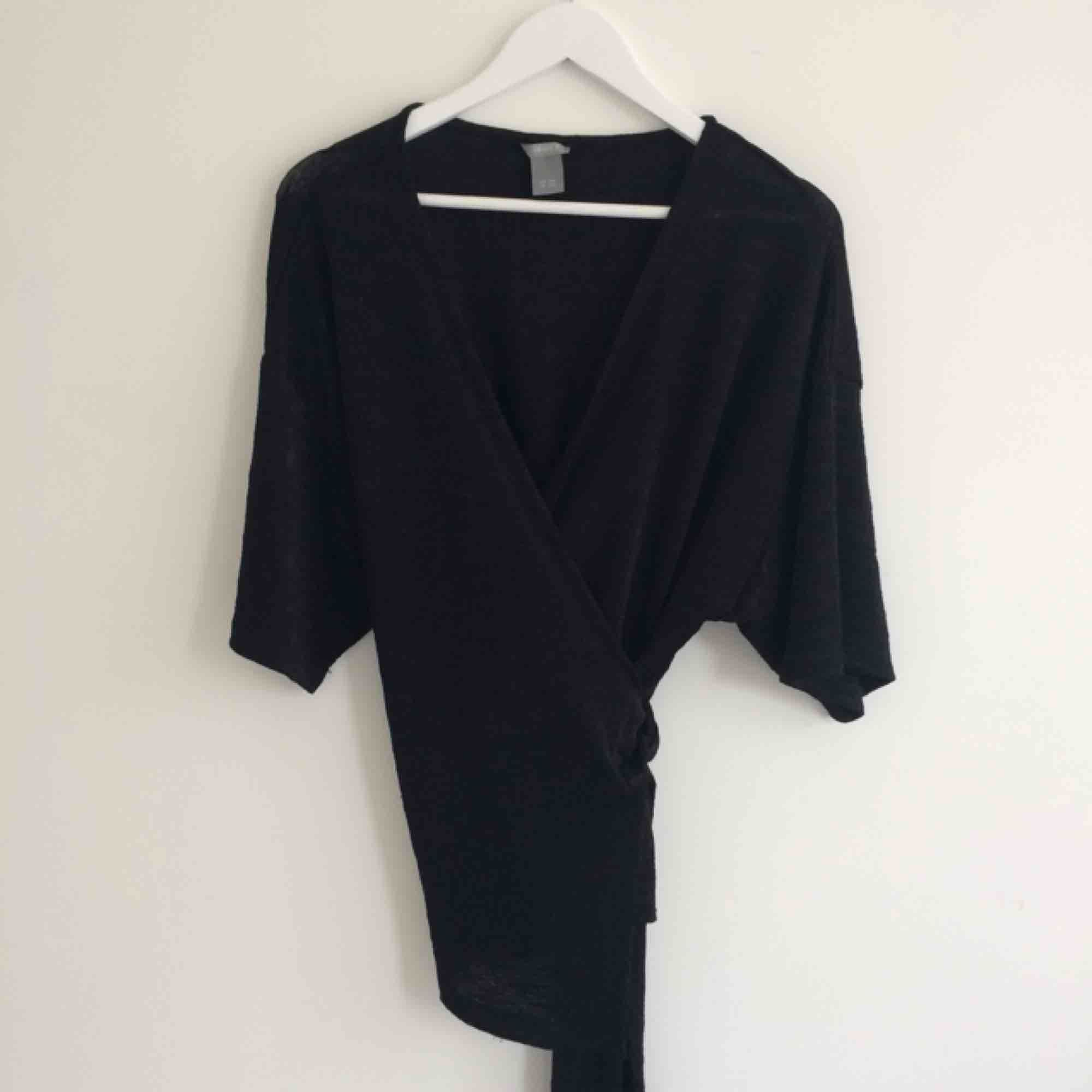 Svart omlottblus/kimono top i skönt material med lite snygg struktur i tyget, se bild 2. Väldigt sparsamt använd! Perfekt till vardags eller festliga tillfällen året runt🌟 . Blusar.