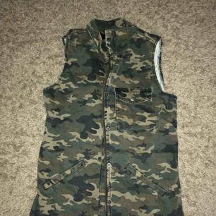 Säljer en jeansväst med militärmönster. Aldrig använd pga inte min stil. Inga slitningar och är i ett bra skick.