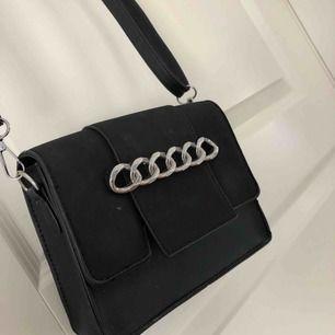 En svart fin handväska, några små märken men som knappt syns. Inga fack invändigt.