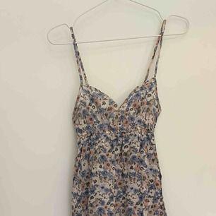 Fotlång klänning, blommig med smala axelband.   Köparen står för porto.