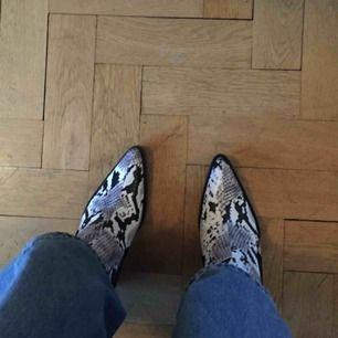 Boots med snakeskinimitation och snygg cowboyklack från Zara, endast använda en gång så de är i toppskick. Storlek 40 men upplevs som en 39a. Frakt 63 kr