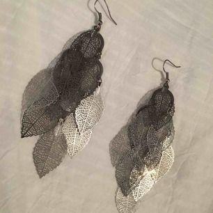 Ett par silvriga örhängen. (Ej äkta silver). Består av små detaljerade silverlöv. De hänger ner 10cm från örat. Jag kan mötas i Uppsala/Täby. Betalning sker via swish/kontant. Kan även posta, men då står köparen för frakten.
