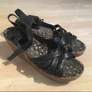 Ett par svarta sandal platå skor. De är i lite slitet skick, speciellt vi spännet (se bild 2).  Jag kan mötas i Uppsala/Täby. Betalning sker via swish/kontant. Kan även posta, men då står köparen för frakten.
