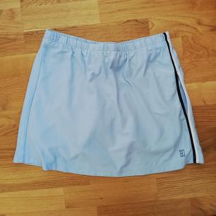 Ljusblå vintage tenniskjol från Nike i stl S. Inbyggda cykelbyxor under så man behöver inte oroa sig för att råka visa trosorna! Sportig rand på ena sidan och dold ficka. Frakt 39 kr.