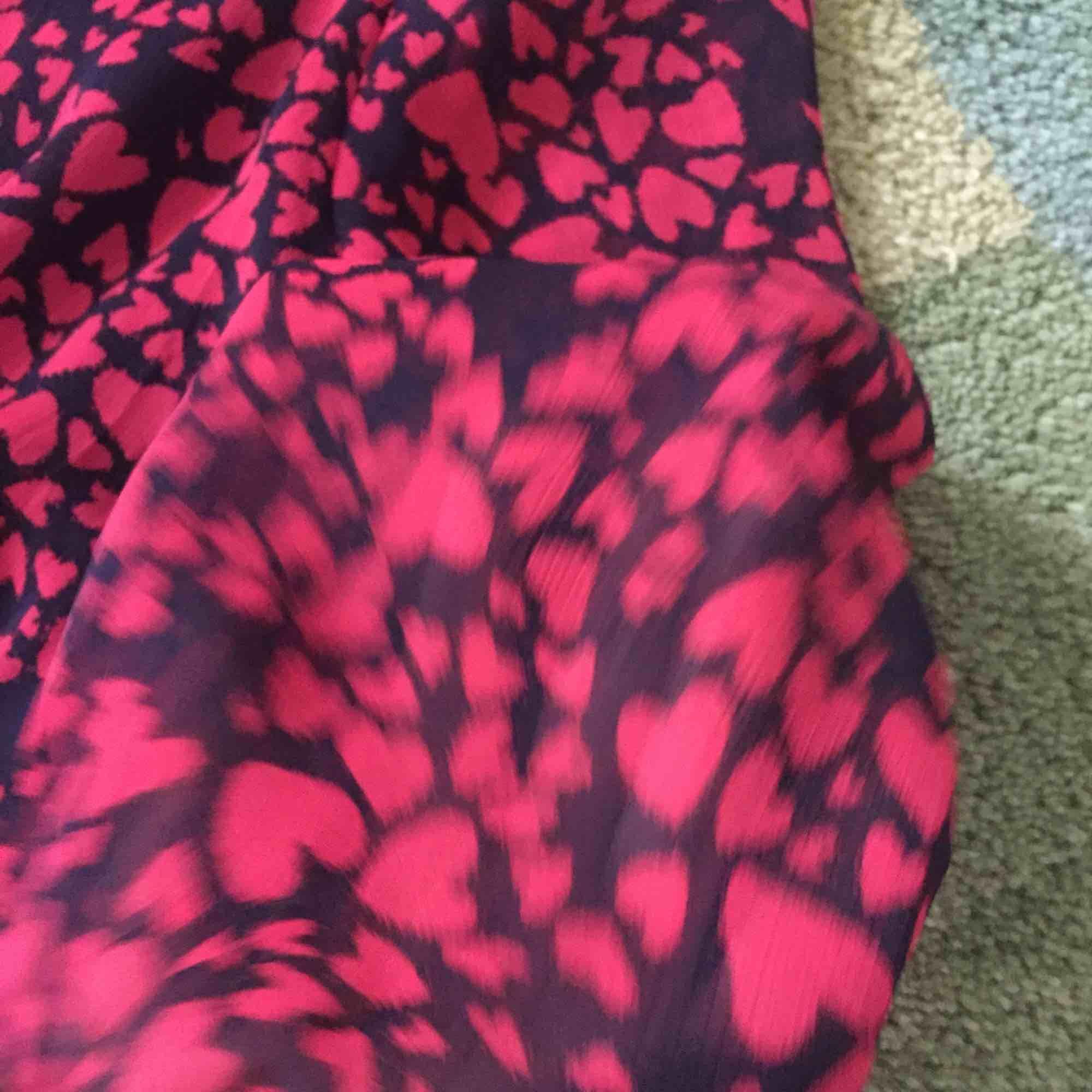 Snygg klänning/tunika från Lindex. Svart bas med mönster av röda hjärtan. Knytband i midjan och lätt transparenta armar.. Klänningar.