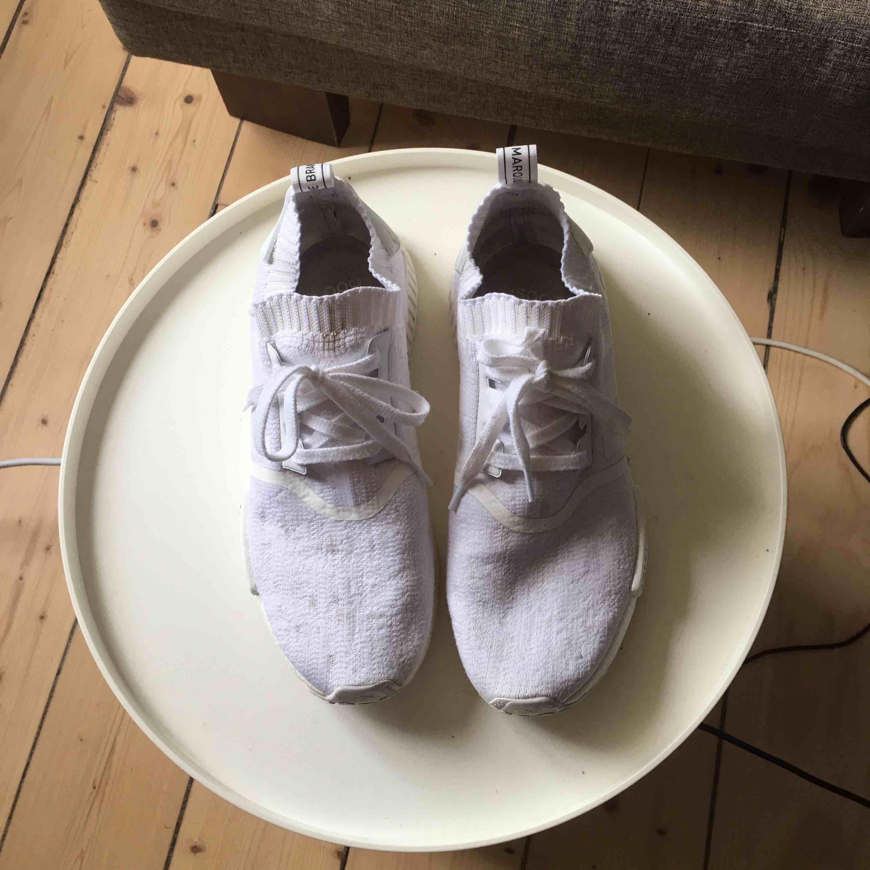 Helt vita Adidas NMD skor, lite smutsiga men det går att bleka bort (testat) för övrigt är dem i hyfsat skick, väldigt bekväma och sköna att ha på sommaren då dem är som en strumpa på foten, pris kan eventuellt diskuteras, frakt ingår. . Skor.