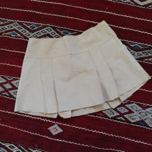 Beige plisserad kort kjol från Saint Tropez i stl XL. Gjord i 100% mocka. Frakt 55 kr.