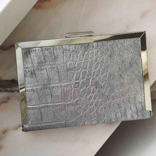En helt oanvänd clutch / väska från märket Atmosphere. Köptes för väldigt mycket & har en kedja som kan göra så att det blir en väska. Ser lyxig och dyr ut och är superfin, perfekt skick. Fin för klänningar osv!