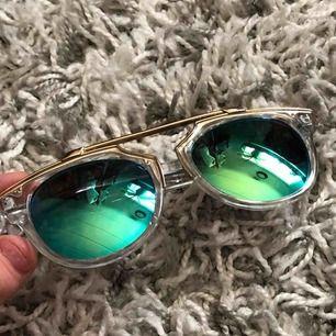 Genomskinliga solglasögon med gullig kant och blå/grön reflektion. Skitsnygga!