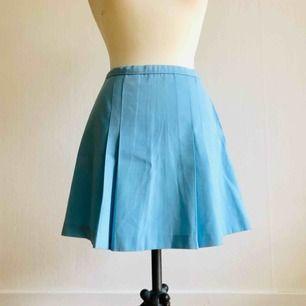 Ljusblå kjol, 60-tal. A-linje. Hög midja, midjeomkrets: 64 cm.  Längd: 40 cm.     Kjolen är i mycket fint, vintage skick.     Frakten ingår i priset. Kan även mötas upp i Malmö!
