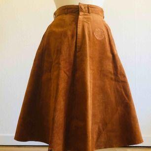 Brun mockakjol, hög i midjan och A-linje.   Har själv köpt vintage och var redan då en liten skada (se bild 3).  I övrigt är kjolen i perfekt skick!   Midjeomkrets: 62 cm Längd: 63 cm  Frakt ingår!