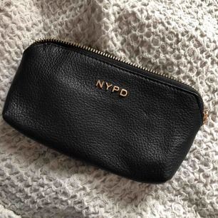 Liten plånbok/clutch från NYPD (New York Portable Design). Köpt något år sedan, endast använd en gång! Finns plats för 2st kort. Guldbokstäver på framsidan och guldig dragkedja. Väldig basic men superfin!