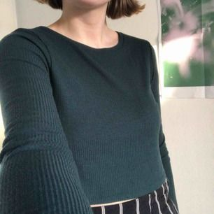 Långärmad tröja i fantastisk mörkgrön färg. Slutar en liten bit över naveln. Passar S-M.