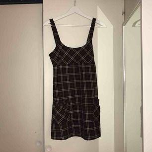 Rutig klänning från märket Pimkie. Två fickor och knappar där bak. Dragkedja i sidan. Står ingen storlek men skulle säga S.