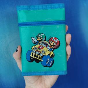 Jättecool super Mario-plånbok från 1990. I helt perfekt skick med tryck fram och bak samt ett mönster genom hela plånboken i en lite ljusare turkos/grå färg. Har plats för sedlar och mynt samt ett fack med dragkedja på utsidan. På längden mäter plånboken cirka 14,5 cm och på bredden (när den är stängd) mäter den cirka 10 cm. Frakten för denna ligger på 18 kr, samfraktar gärna! ☺️👍 (mer fraktkostnad kan tillkomma vid köp av flertalet varor)