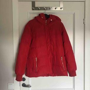 Röd vinterjacka. Supervarm, har ett litet hål i en ficka annars typ oanvänd. Köparen står för frakt