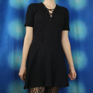 Jättefin ribbad kort svart klänning med snörning i halsen. Frakten för denna ligger på 36 kr, samfraktar gärna! 👍☺️ (mer fraktkostnad kan tillkomma vid köp av flertalet varor)