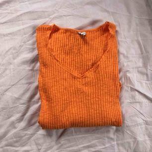 Orange ribbad v-ringad långarmad tröja som är rundad längst nere. Köpt på Nelly, använd en gång