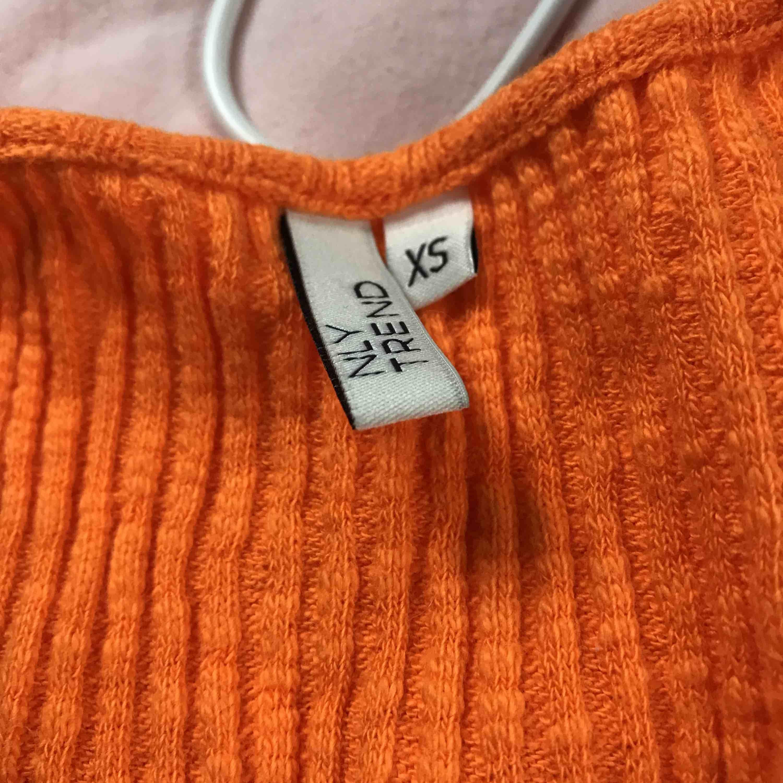 Orange ribbad v-ringad långarmad tröja som är rundad längst nere. Köpt på Nelly, använd en gång. Toppar.