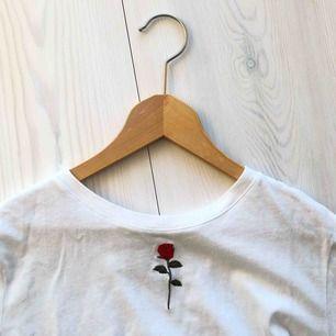 T-shirt med broderad ros vid halsen. Frakten på denna är endast 35 kr!