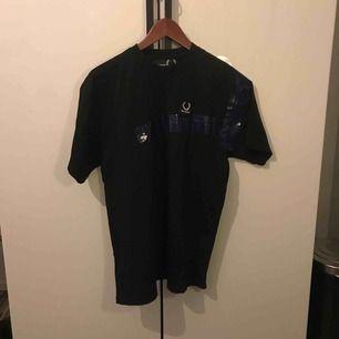 Raf Simons x Fred Perry t-shirt med blå tejp på framsida och lite på baksidan av t-shirten. Använd endast ett fåtal gånger, är lite för stor för mig men ger en snygg oversized look! Nypris: 1100-1500kr