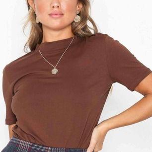 Brun high neck t-shirt från Nelly i storlek M. Mycket fint skick, knappt använd. Fraktar ej men möts gärna upp och betalningen sker via Swish.