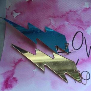 Skitballa blixt-örhängen som har olika färg på olika sidor samt speglar. Inköpta på buttericks använda 2 gånger.