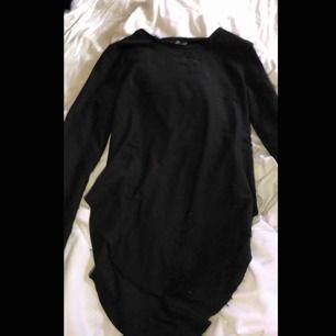En lång tröja om man inte vill ha den som kort klänning, längre bak än fram o slitsar på sidorna, slitningar över hela tröjan men visar inte hud