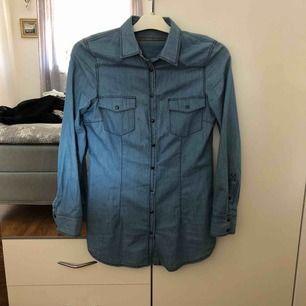 Lång tun jeans skjorta, topp knappen saknas. Frakt tillkommer
