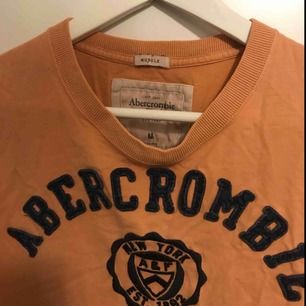 Super snygg T-shirt i orange/beige från Abercrombie, sitter som en oversize T-shirt på mig som vanligtvis har XS/S