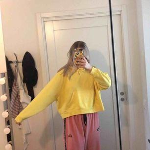 Gul cropped hoodie med en ficka över magen. Storlek S