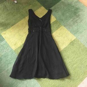 Vacker v-ringad klänning med fint paljettbälte