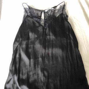 Svart silkes linne med spets kant och brottar rygg från ginatricot, storlek 36/S. Använd men i väldigt gott skick. Möts gärna upp eller skickas mot frakt!