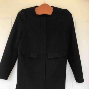 Sort frakke med to yderlommer. Velegnet til efterår og forår. Lidt håret på billedet, men det er vasket og rengøres ordentligt, før man køber. Kan gå ned i pris på hurtig butik;)