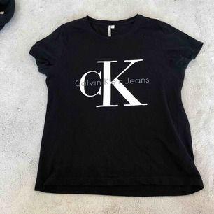 En svart T-shirt från Calvin Klein. Har tre små hål på framsidan som knappt syns, se bild 2.