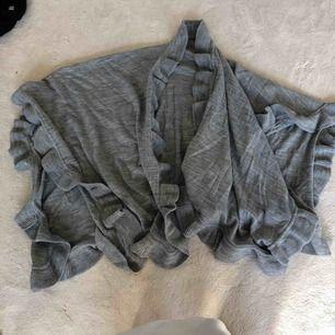 En grå sjal/poncho från Åhléns, knappt använd.