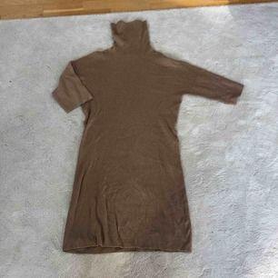 En  oanvänd beige ribbad klänning från Massimo Dutti med polokrage
