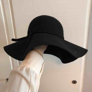 Fin, svart yllehatt med ett band runt i ylle också. Säljer pga använder aldrig hatt längre! Fint skick.