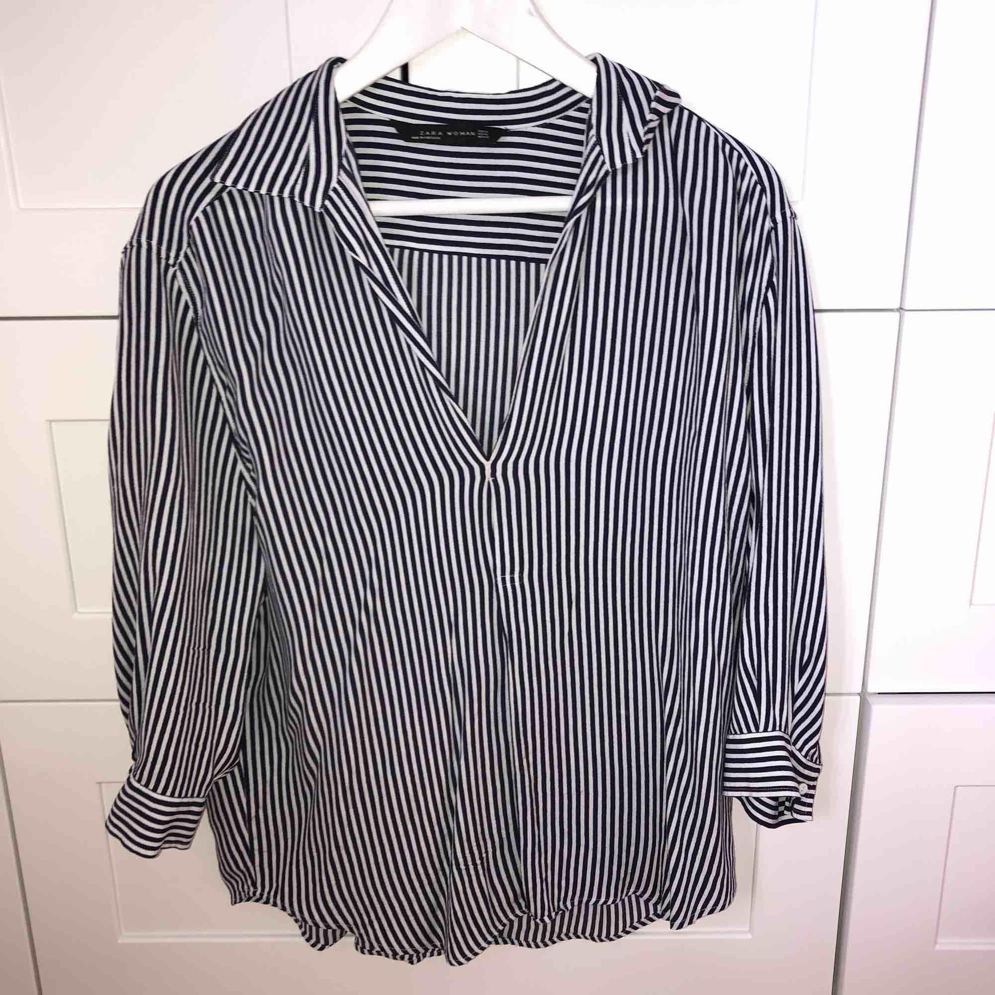 En blå och vit randig skjorta i blusmaterial från Zara. Blusar.