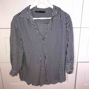 En blå och vit randig skjorta i blusmaterial från Zara