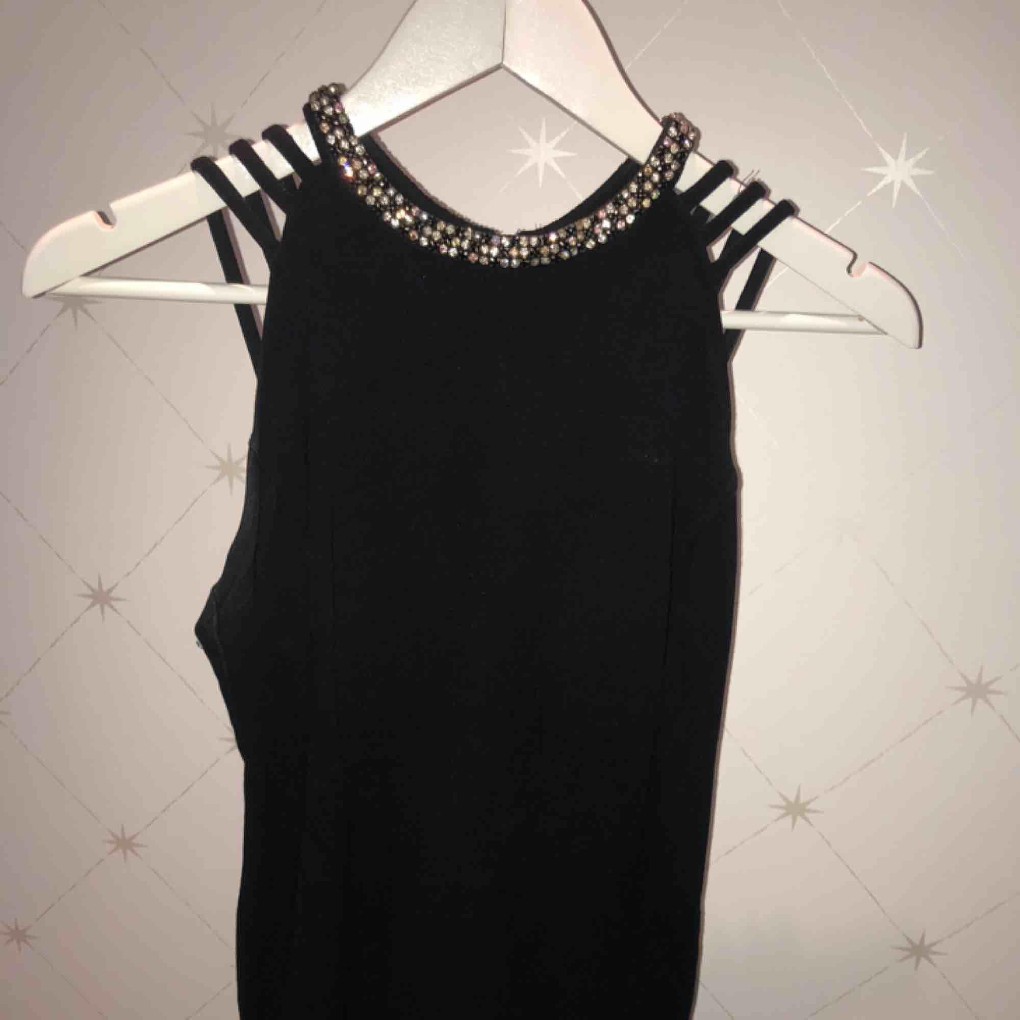 Svart festklänning med öppen rygg och korsade band. Vid halsen är det små kristaller som toppar allt🌟 storlek 36 och säljs billigt. Ursprungspris 1299kr. Klänningar.