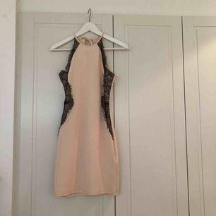 Ljust puderrosa/pesikofärgad klänning med svart spets från Nelly.com i storlek S.