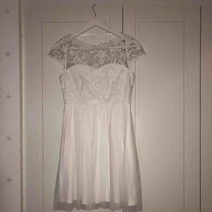 Supergullig studentklänning som är helt oanvänd. Vit spets över hela klänningen och tyll i botten. Ryggen är öppen med vit spets!
