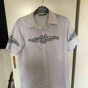 En kortärmad skjorta köpt från humana med tribalmönster på bröst och ärmar Kan mötas upp i Stockholm! Annars betalar köparen för frakt ⭐️
