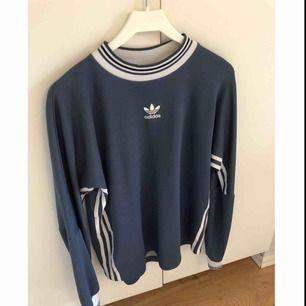 Tjockare långärmad tröja ifrån Adidas. Herrstorlek S men sitter snyggt oversize om man knyter upp den. Köpt ifrån Plick tidigare men säljes nu för den inte kommer till användning längre. Bra skick. Frakt betalar köpare.