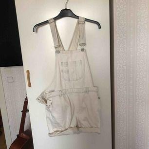 ett par vita hängselshorts i jeansmaterial från Never Denim
