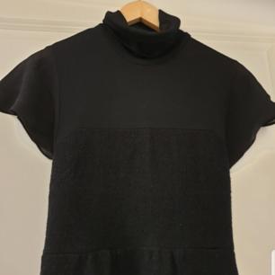 Svart klänning med hög hals kjolen är i tjockare ull tyg